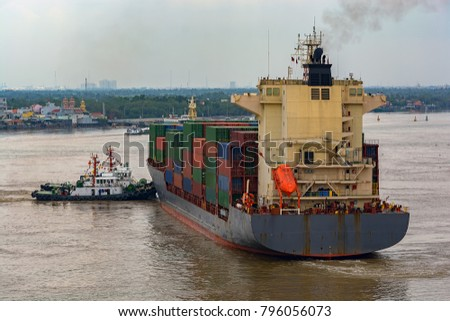 Tug boats assist the container vessel to turn down the Long Tau River near the Ho Chi Minh City. Vietnam, Southeast Asia.