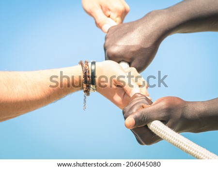 Tug of war - Concept of interracial multi ethnic union together against racism - Multiracial hands teamwork - stock photo