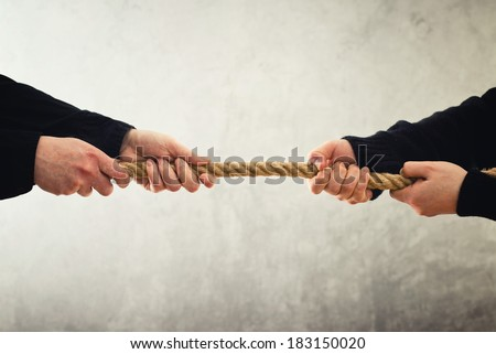 Tug of war. Female hands pulling rope to opposite sides. Rivalry concept. - stock photo
