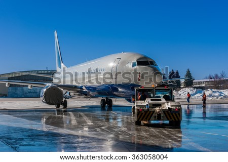 TUG Pushback tractor carries a passenger jet out of hangar at Vnukovo Airport - Moscow, February 18, 2015 - stock photo