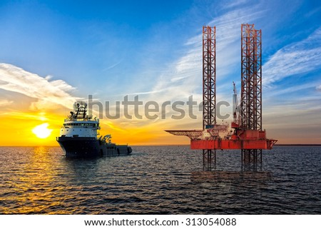 Tugboat and Oil Platform on offshore area at sunset.
