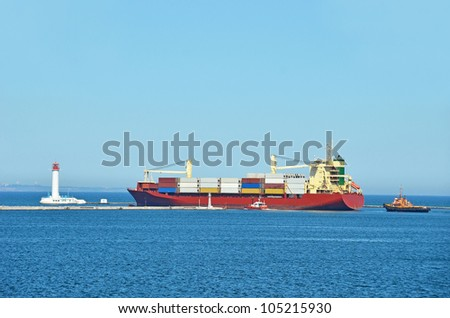 Tugboat assisting cargo ship over lighthouse in Odessa, Ukraine - stock photo