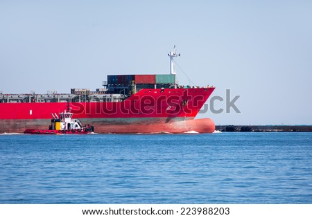 tugboat assisting huge vessel