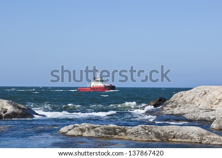 Tugboat at rocky coast - stock photo