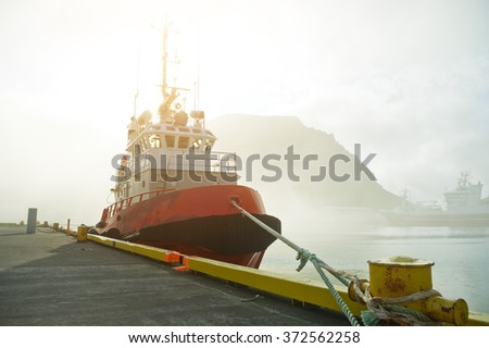 Tugboat in harbour on a misty day