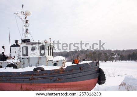 Tugboat in Winter - Rustic, weathered  tugboat sitting in snow.  Waiting for Spring.  Copy space in upper right of frame. - stock photo