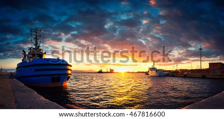 Tugboat moored in harbour at sunset