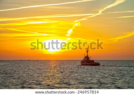 Tugboat on sea in the rays of the setting sun.  - stock photo