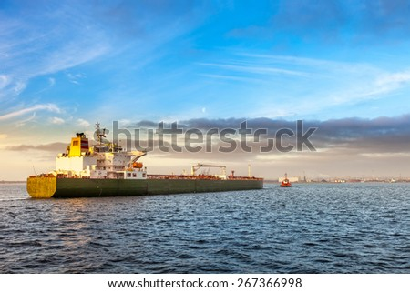 Tugboat pulling the tanker at sea in the morning.  - stock photo