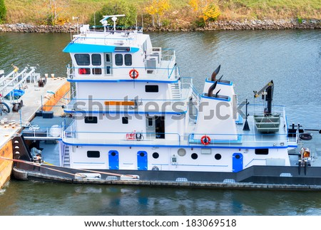 Tugboat pushing a barge in Tennessee-Tombigbee Waterway. - stock photo