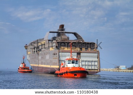 Tugboats assisting huge semi finished vessel to be transported from one shipyard to another - stock photo