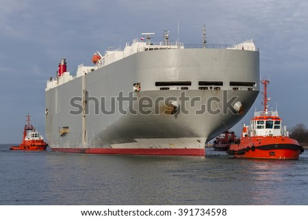 Tugs bring the ship into port - stock photo