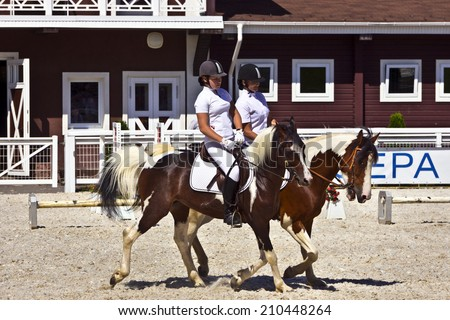 TULA, RUSSIAN FEDERATION - JUNE 12, 2014: Pair of pinto coloured horses with female riders at the Groumant Horse Show. - stock photo