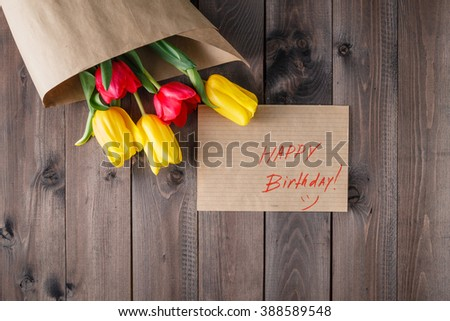 Tulip bouquet in craft paper on wooden table, message happy birthday