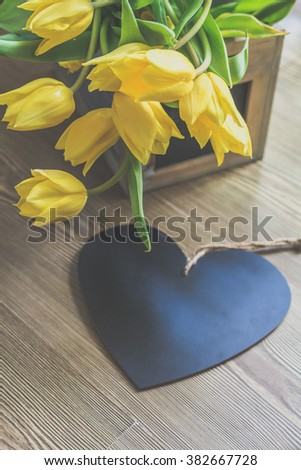 Tulip flower arrangement in a wooden container with a black wooden heart
