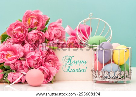 Tulip flowers and pastel colored easter eggs. Festive decoration with greetings card and sample text Happy Easter! - stock photo