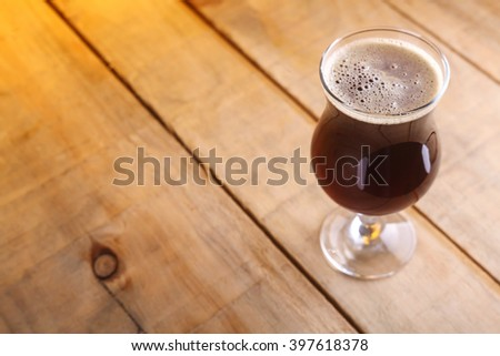 Tulip glass with dark brown beer on a grunge wood surface - stock photo