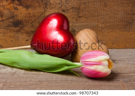 Tulip, red heart and wooden heart on a plank, with wooden wall in the background.