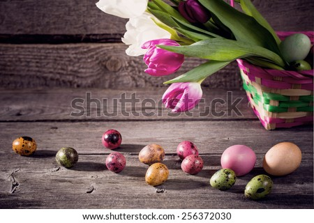 tulips and easter eggs on wooden background - stock photo