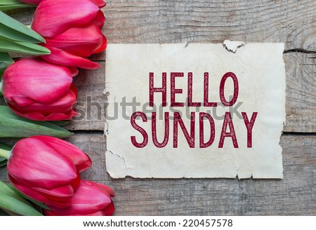 Tulips and paper with text Hello Sundayon wooden table - stock photo
