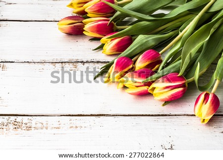 Tulips arrangement on a wooden background for mothers day, wedding invitation, greetings card and invitation cards - stock photo
