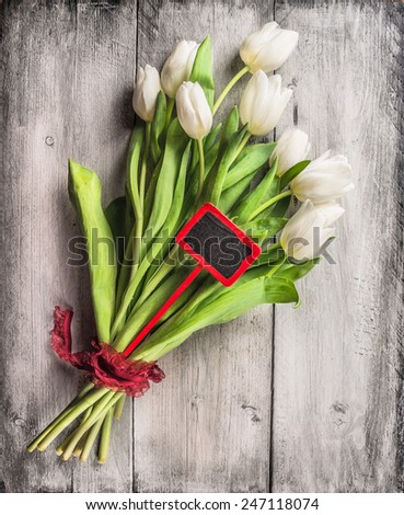 Tulips bouquet with red sign and ribbon on gray wooden background, top view - stock photo
