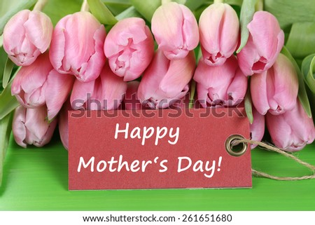 Tulips flowers with a sign and the text Happy mothers day - stock photo