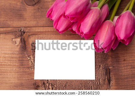 Tulips flowers with greeting card over wooden table - stock photo