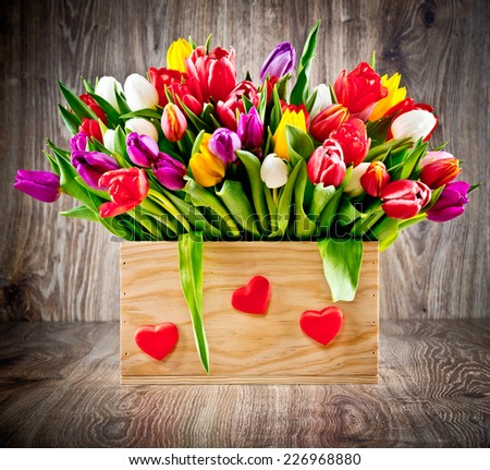 Tulips in the box on wooden background - stock photo