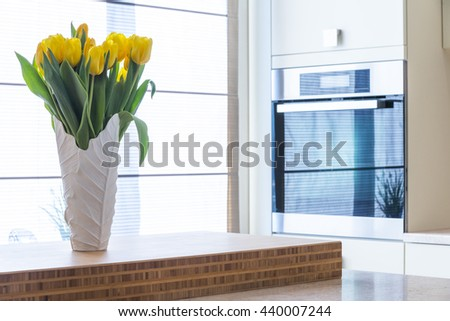 Tulips in the vase on a kitchen table