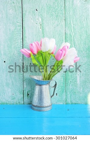 Tulips in vase on vintage table. - stock photo