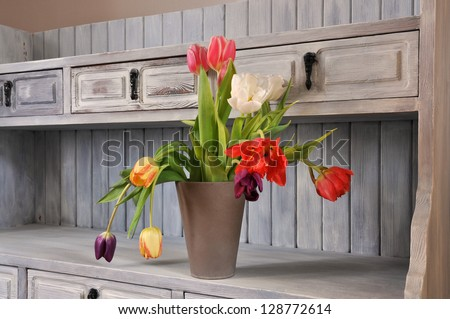 Tulips on an old fashioned bookshelf in shabby chic, - stock photo