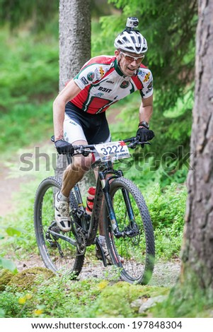 TULLINGE, STOCKHOLM - JUNE 8: Mountain bike cyclist in forest trail with camera on helmet at Lida loop race 2014 during a sunny day in the Swedish nature. June 8, 2014 in Stockholm, Sweden. - stock photo