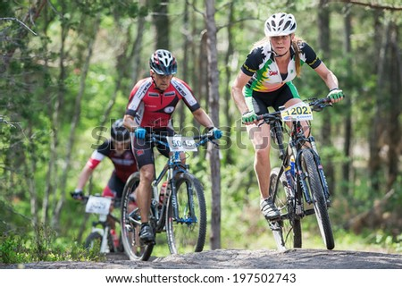 TULLINGE, STOCKHOLM - JUNE 8: Woman mountain bike cyclist thru a rocky section in the forest at Lida loop race 2014 during a sunny day in the Swedish nature. June 8, 2014 in Stockholm, Sweden.