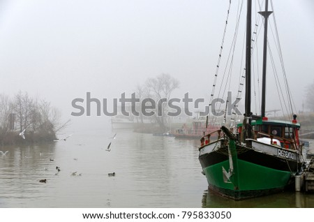 "TULLN, AUSTRIA - JANUARY 6, 2018: Sailing ship ""Rainy day"" of the deceased artist Friedensreich Hundertwasser on a foggy day in the harbour at the river Danube"