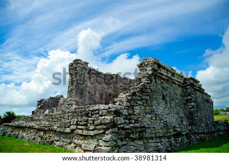 Tulum architecture represented by the remnant of a rocky structure emerging from a solid base of stone against a bright blue sky with puffy white cumulus clouds - stock photo