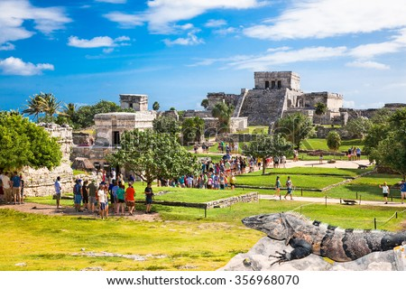 TULUM, MEXICO - NOVEMBRE 26. 2015:The crowd Iguanas watching the tourists who visit Tulim in Yucatan, Mexico on November 26, 2015. Over 1.2 million tourists visit the ruins every year. - stock photo