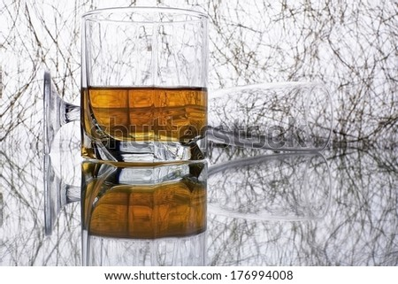 Tumbler of golden whiskey or brandy and empty glass on the original background  with reflection - stock photo