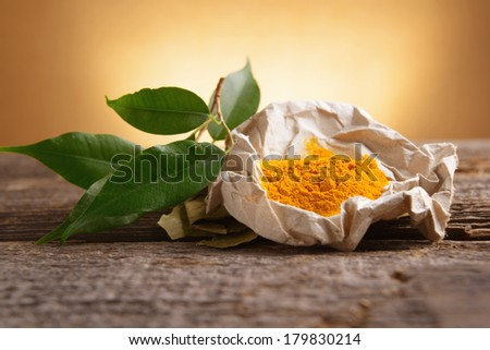 Tumeric powwder spice on wooden board with fresh leaves - stock photo