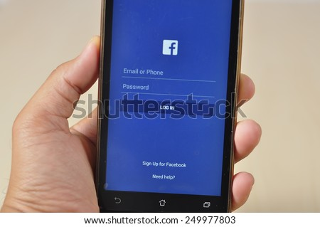 TUMPAT,KELANTAN - FEBRUARY 4, 2015 : Hand holding phone to log in face Facebook. Facebook is a social media online service for microblogging and networking communication.