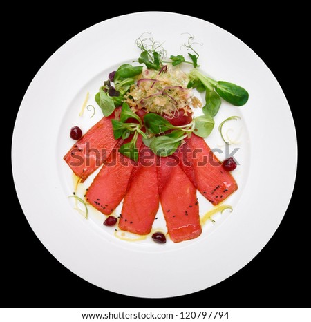 Tuna carpaccio on plate isolated on black background - stock photo