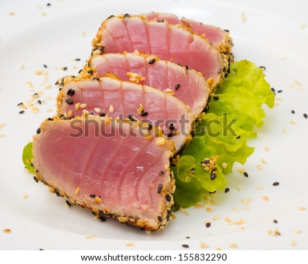Tuna fillet with sesame soy sauce on a big white plate - stock photo