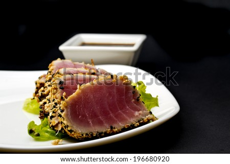 Tuna fillet with sesame soy sauce on a big white plate over black background - stock photo