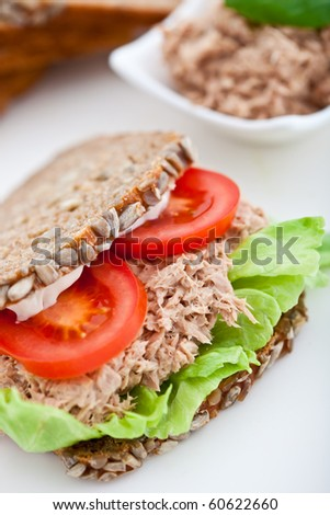 Tuna fish sandwich with tomatoes, lettuce and mayonnaise on a wooden board. Shallow DOF - stock photo