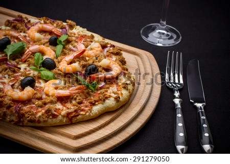 Tuna pizza with shrimp and black olives, top view - stock photo