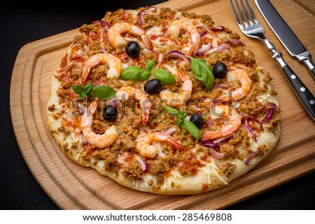 Tuna pizza with shrimp and olive, cutlery, top view - stock photo