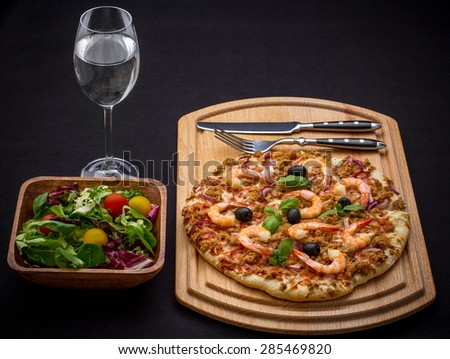 Tuna pizza with shrimp and salad, cutlery, top view - stock photo