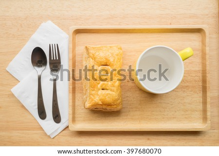 Tuna puff pasty with yellow empty mug on a wooden plate with fork, spoon and white tissue paper on the left - top view with outdoor lighting - stock photo