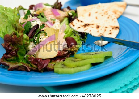 Tuna salad on a bed of Red Leaf Lettuce with Artichoke hearts, Kalamata olives, red onions and Feta Cheese, Kiwi slices and pita bread served on a turquoise colored plate