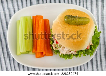 Tuna salad sandwich with lettuce on a homemade bun with healthy carrot and celery sticks and a pickle - stock photo